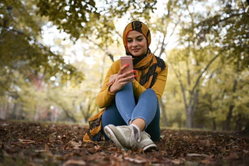 happy young woman sitting in forest and typing on phone