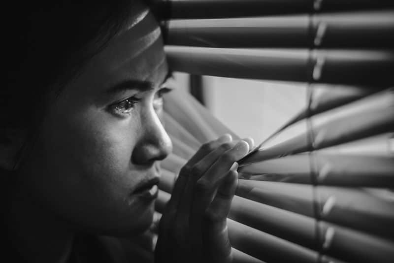 black and white picture of a jelous asian woman looking through th window