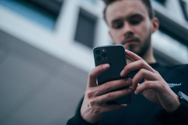 man looking at phone outside