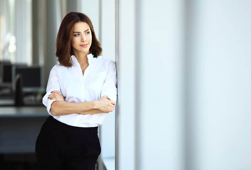 modern business woman with her arms crossed in a white shirt