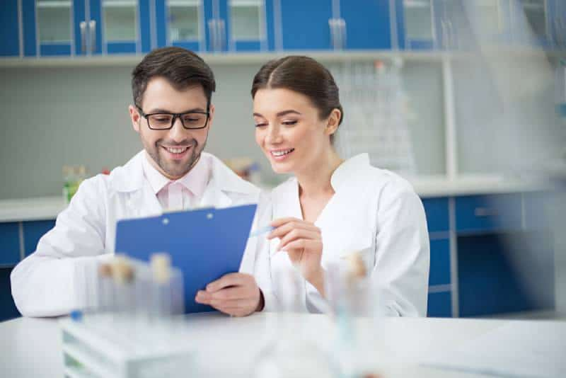 portrait of smiling scientists writing in notepad in lab
