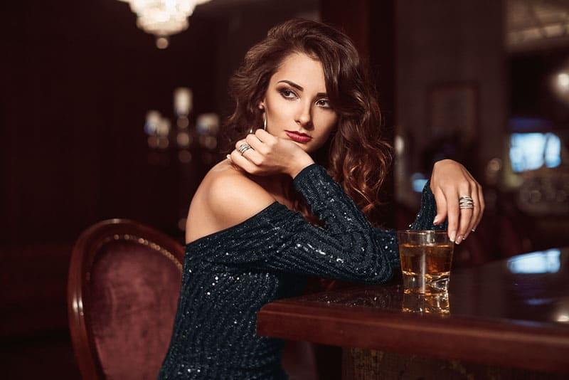 young woman drinking whiskey in a bar
