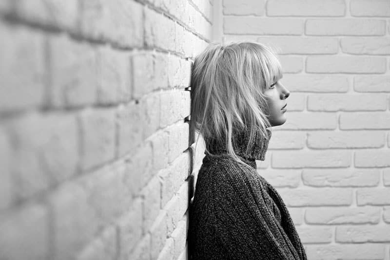 black and white picture of a sad young blonde woman leaning against the wall