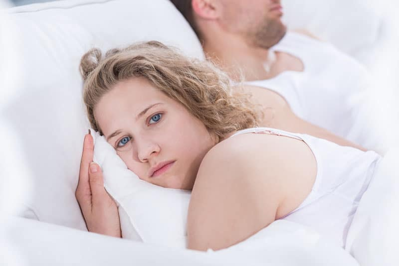 sad young couple not talking to each other while laying in the bed