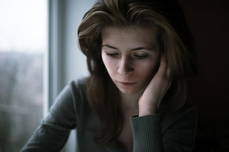 sad blonde woman by the window crying
