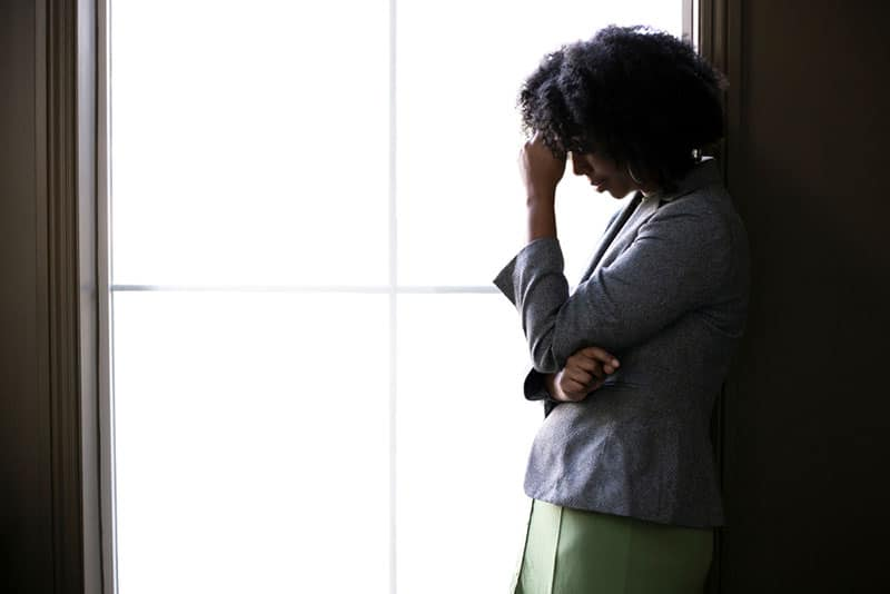 sad black woman crying by the window