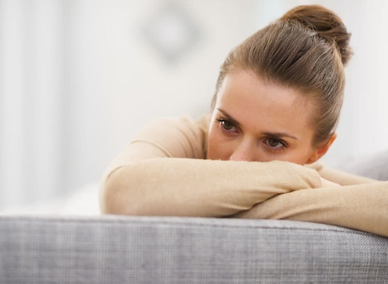 sad young woman sitting on couch and covering her face with her arm
