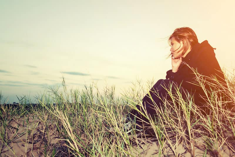 sad woman sitting in the field