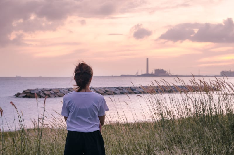sad woman standing near sea