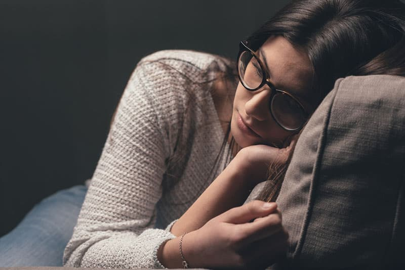 sad woman with glasses sitting on the couch
