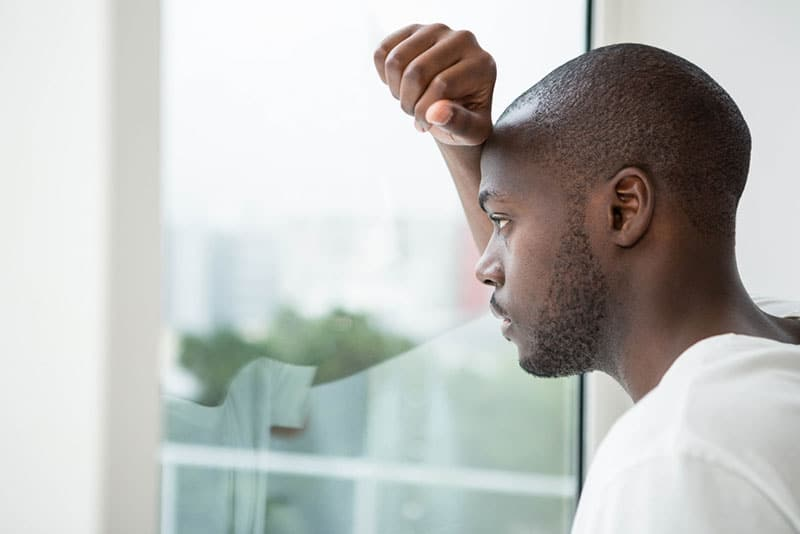 sad young black man looking through the window