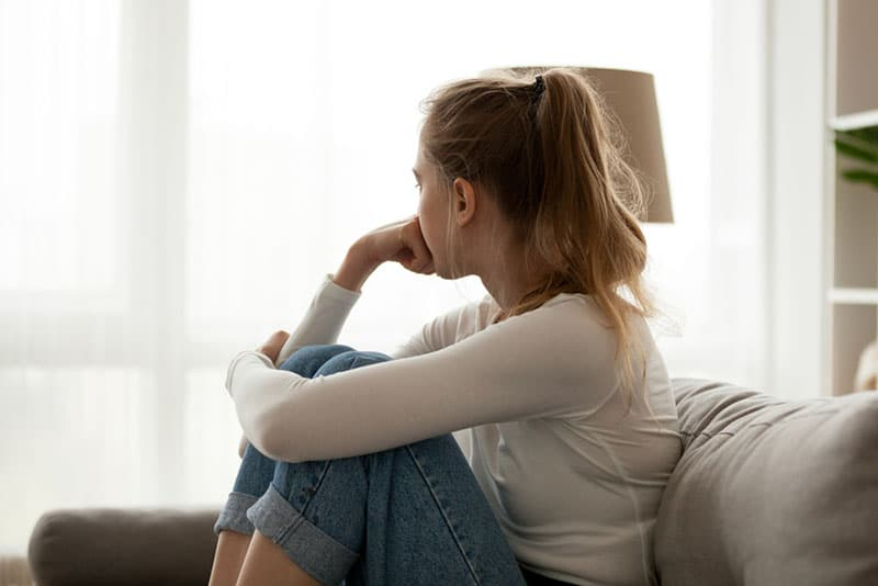 sad young blonde woman sitting on couch and looking through window