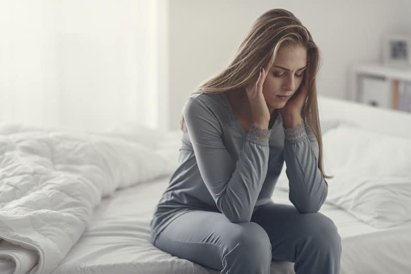 sad young blonde woman sitting on bed