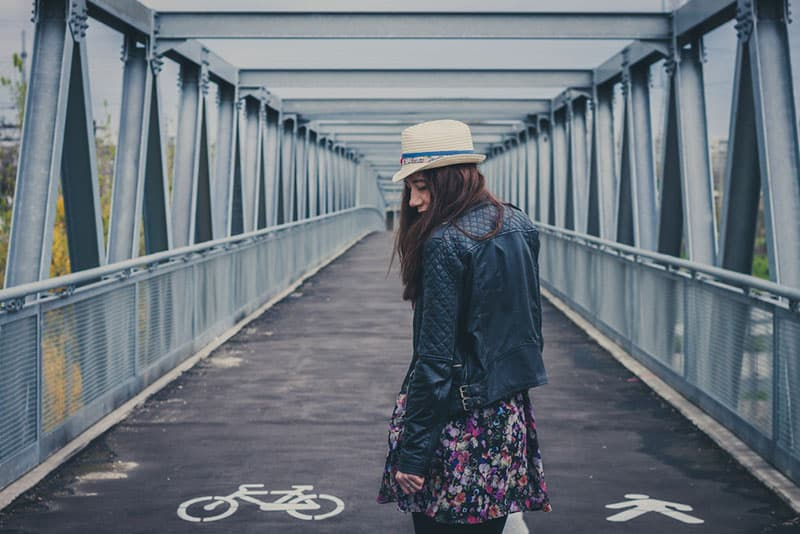 sad young redhead woman standing on the bridge