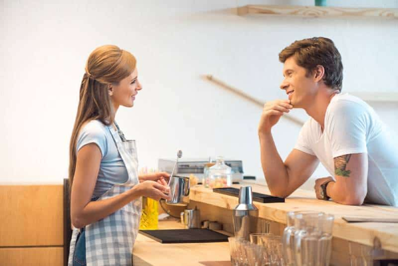 side view of young man and woman flirting in cafe