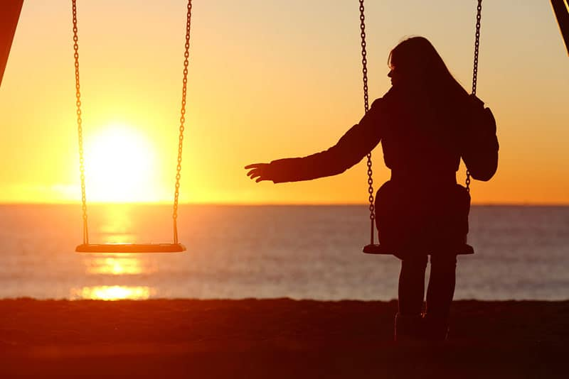 silhouette of a lonely woman sitting on a swing set by the ocean