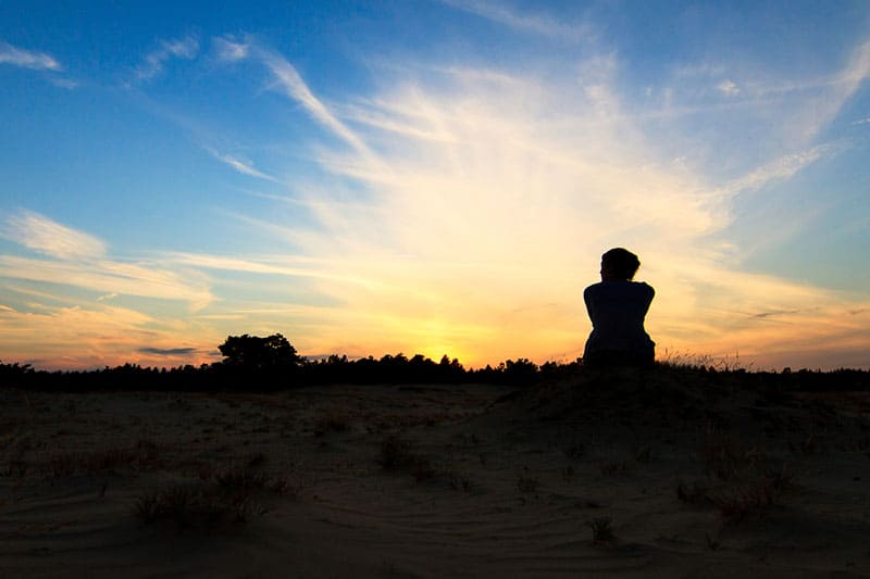 silhouette of a woman in susnet sitting in a national park
