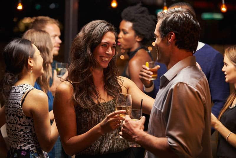 smiling man and woman talking at bar