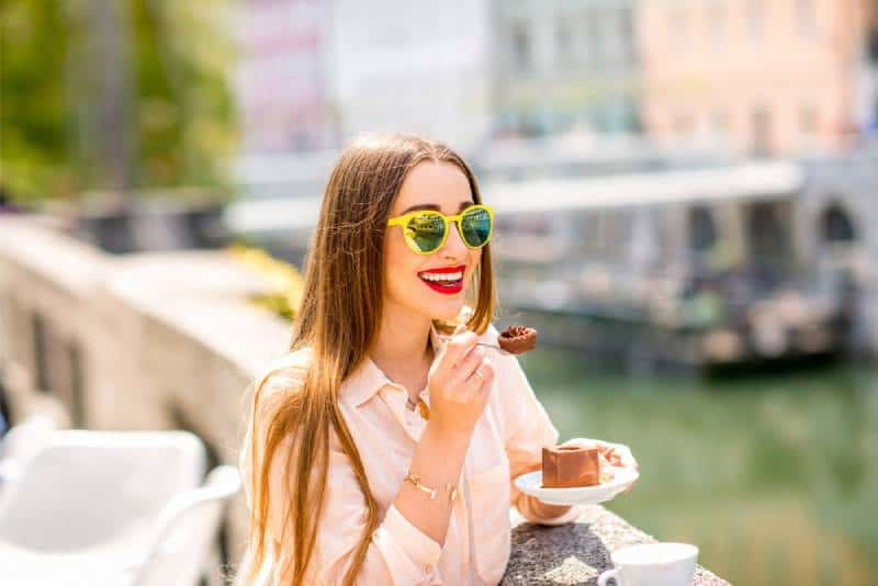 smiling woman eating chocolate cake near the river