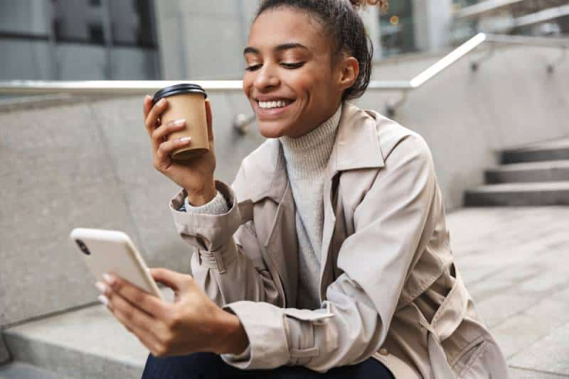 smiling woman holding typing on her phone while holding a cup