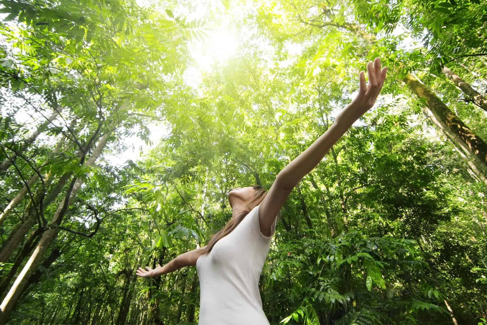 the woman stands in the woods with her arms outstretched