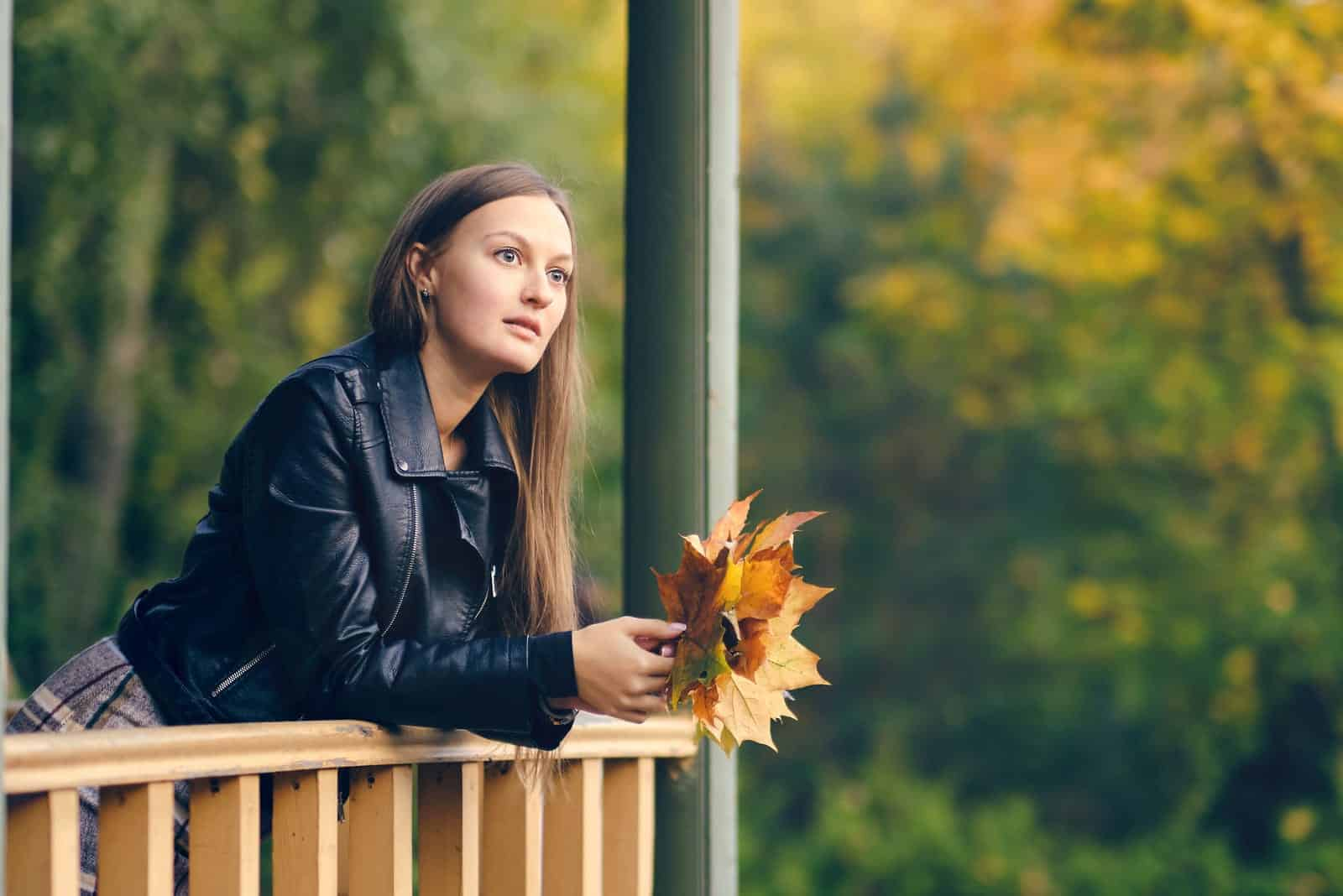 the woman stands on the terrace with leaves in her hands and thinks anxiously