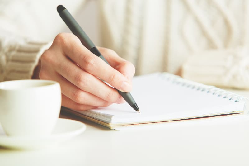 woman in white pullover writing notes