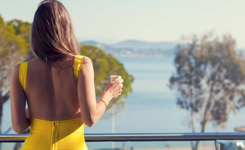 lonely woman in a yellow dress on a balcony next to water
