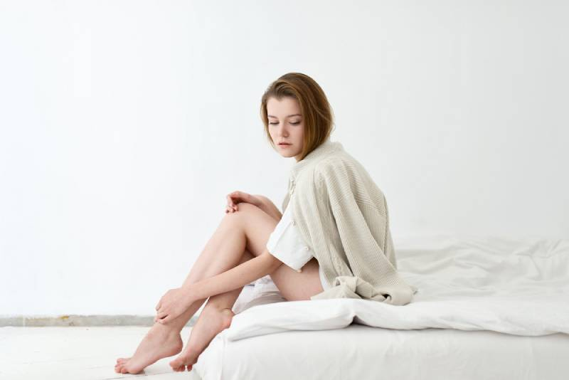 woman sitting on bed look thoughtful