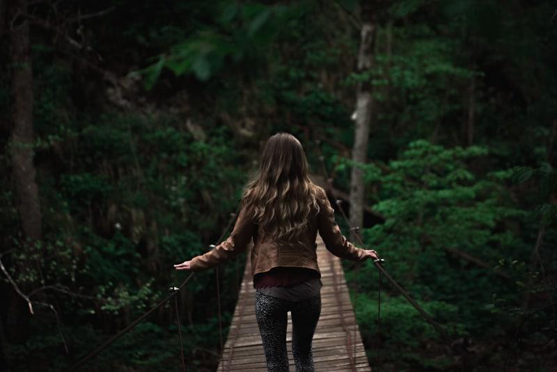 woman trying to pass bridge