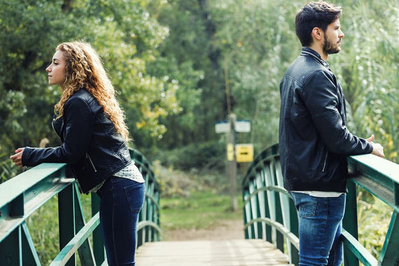 young couple not talking to each other on the bridge
