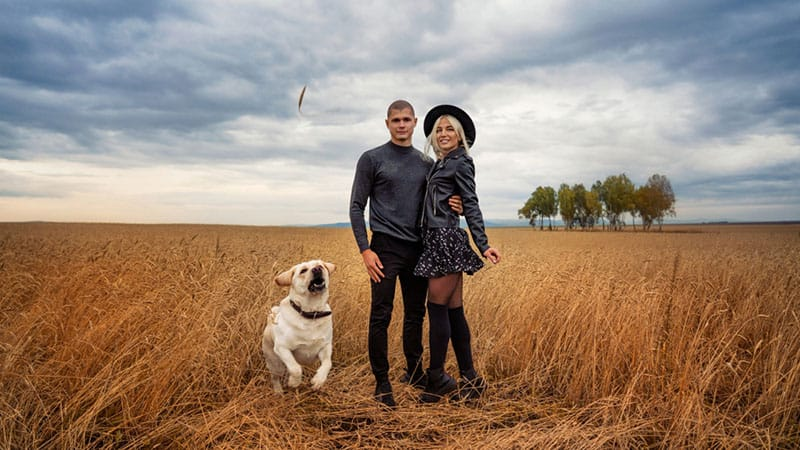 young couple with a dog hanging out in a field