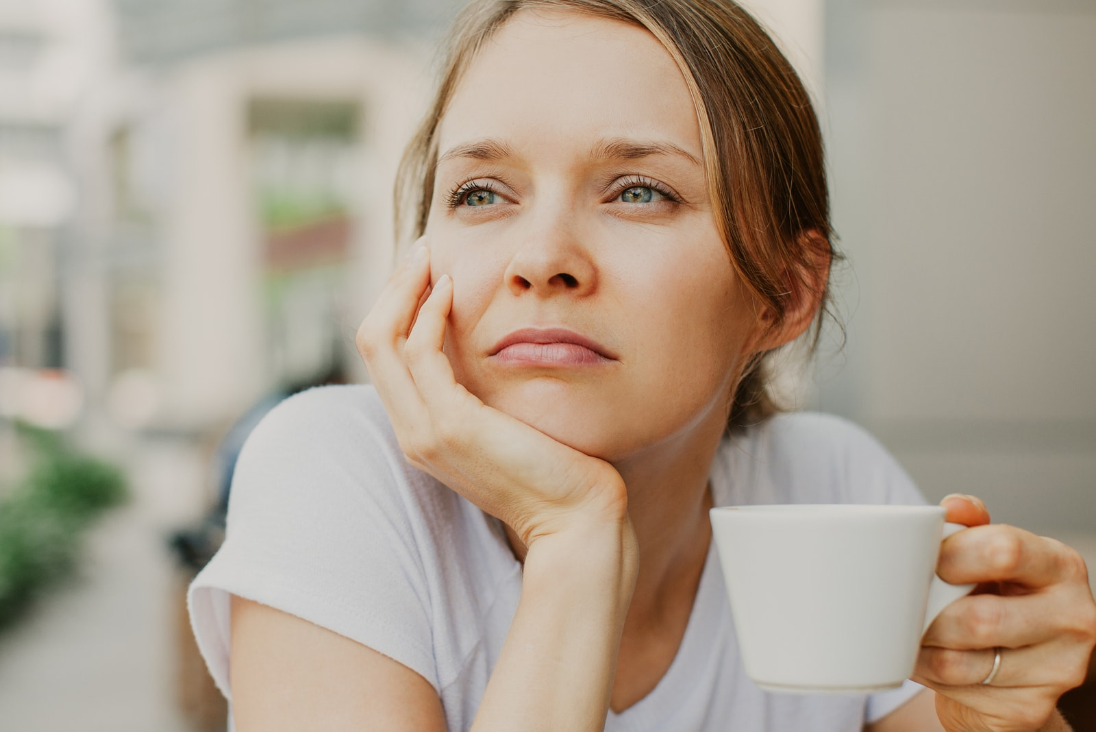 young pensive woman drinking coffee