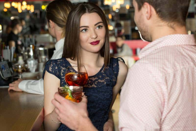 young woman looking straight in the eyes of young man at the bar