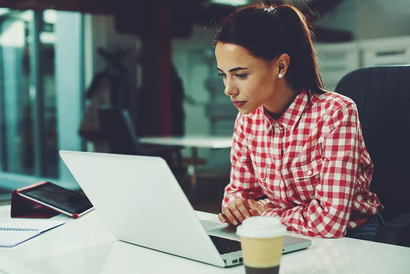 young girl busy with work on her laptop