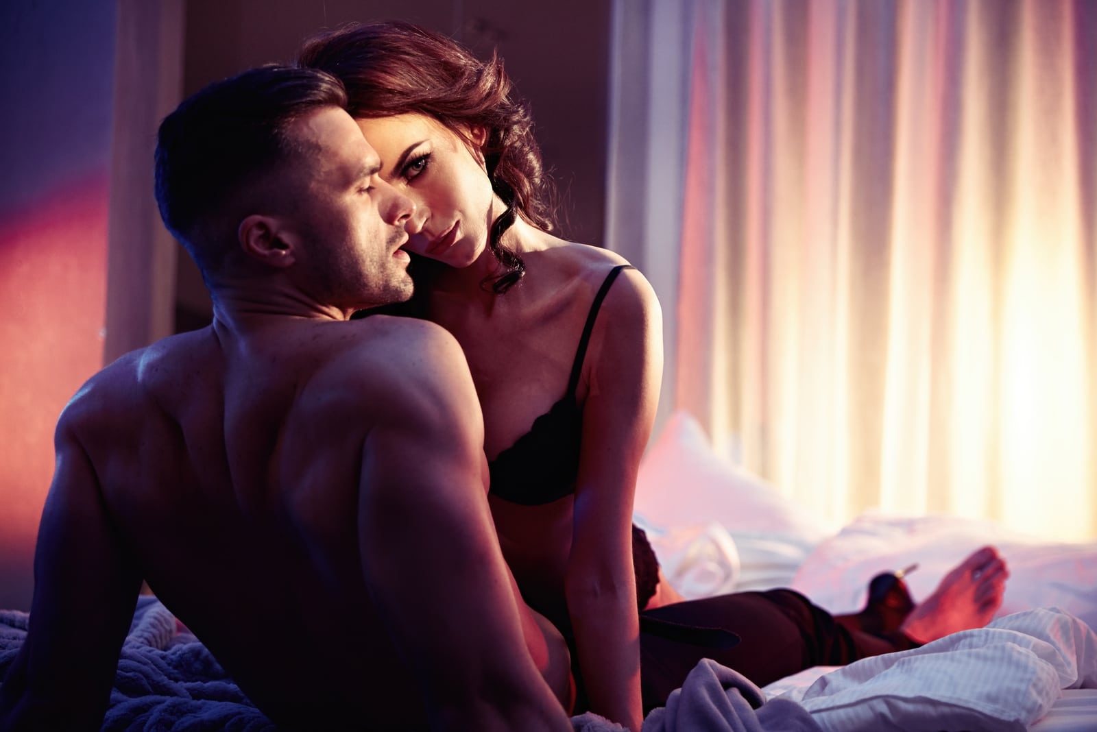 An attractive couple in underwear is lying in bed