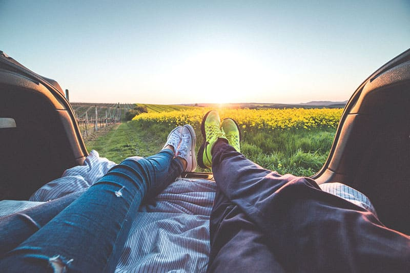 2 people sitting showing feet and yellow flower fields