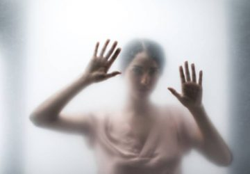 Silhouette of woman behind glass and touching it with hands