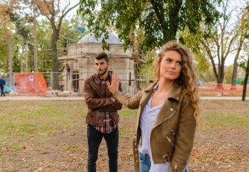 blonde woman showing stop sign to a man in the park