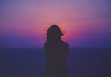 silhouette of woman stynding by the sunset