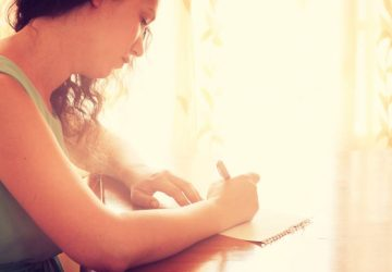 sad girl writing a letter at home