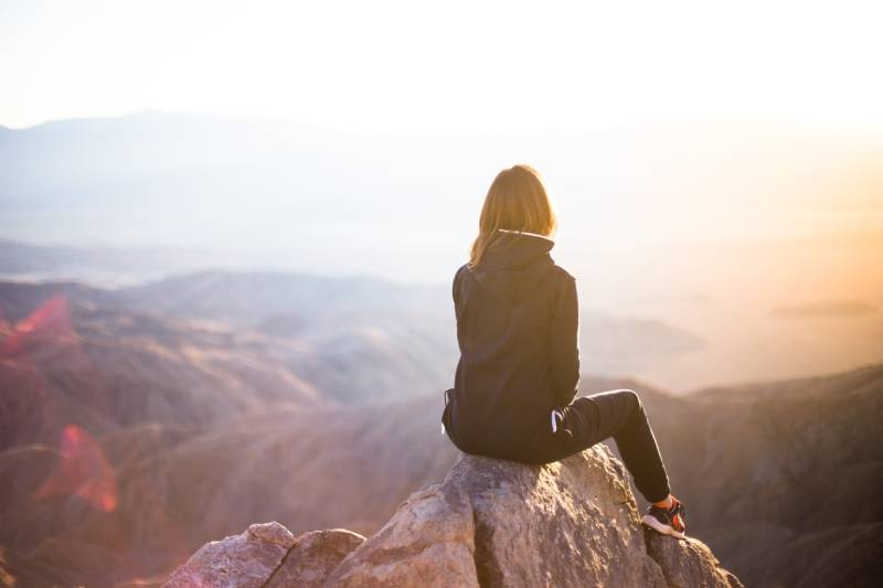 woman sitting on top of mountaim at sunset