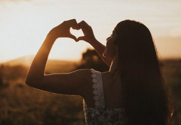 young girl making a heart with her hands on the sunset