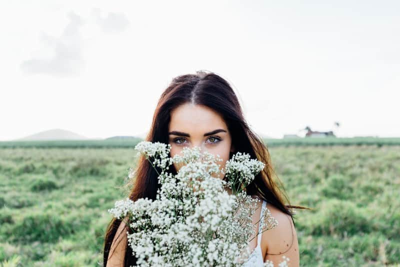 Woman holding white flowers outdoor