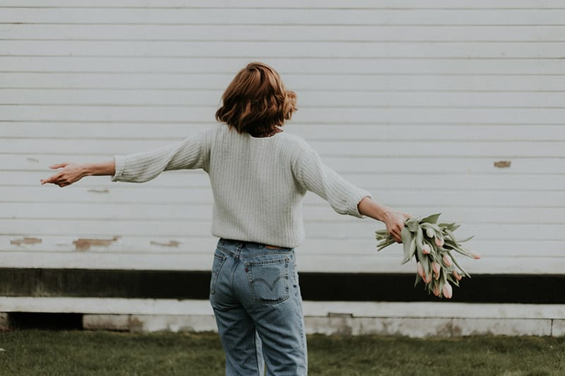 Back of female with arms spread out holding bouquet of tulips