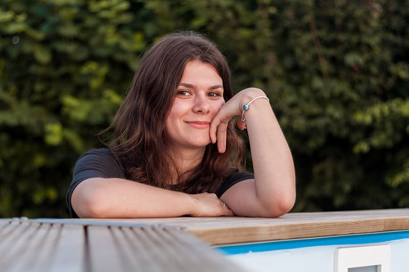 Female smiling hand on cheek while leaning on wooden deck