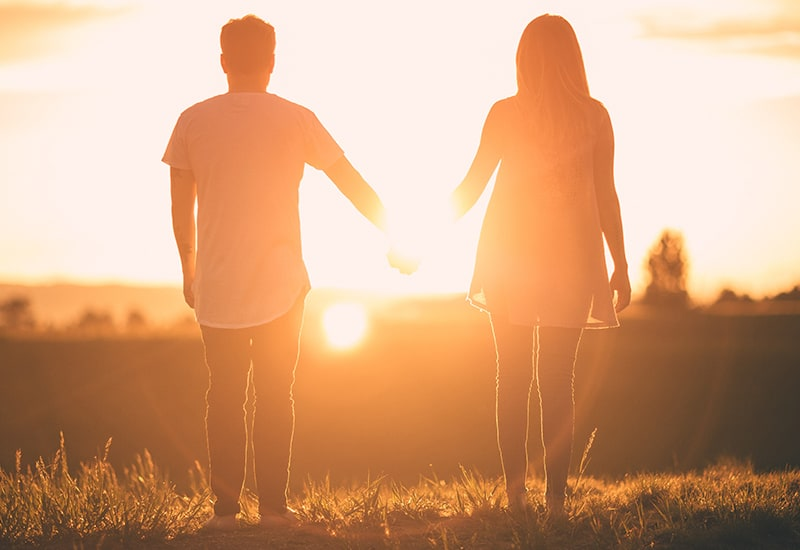 Couple holding hands facing the sunset
