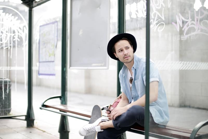 man in blue shirt and hat sitting on a bench