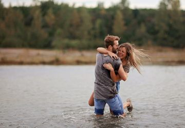man hugging laughing woman while standing in water