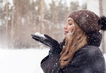 beautiful woman blowing the snow